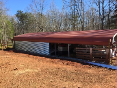 Covering up one side of our carport barn with metal roofing.